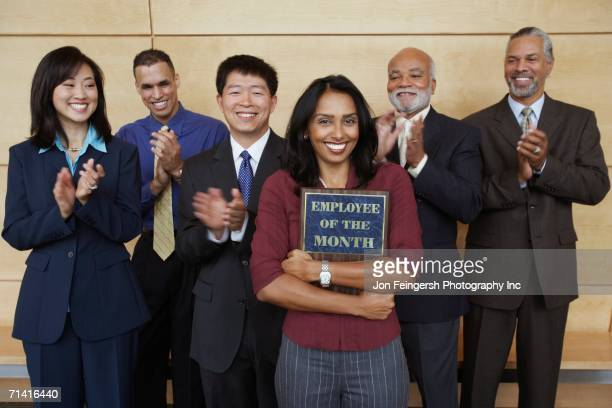 Businesswoman holding Employee of the Month plaque with co-workers applauding