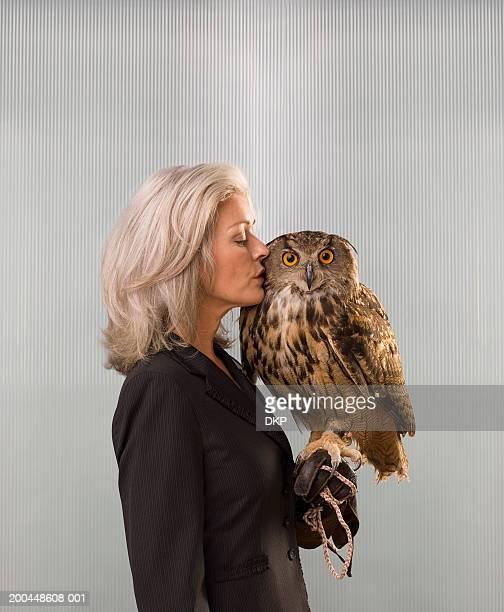 Businesswoman holding Eurasian Eagle Owl (Bubo bubo), kissing head