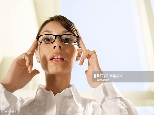 Businesswoman holding eyeglasses on her face