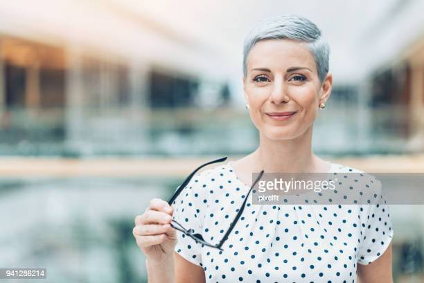 businesswoman holding eyeglasses - occhiali da vista foto e immagini stock