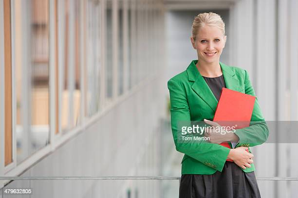 businesswoman holding file - green coat stock pictures, royalty-free photos & images