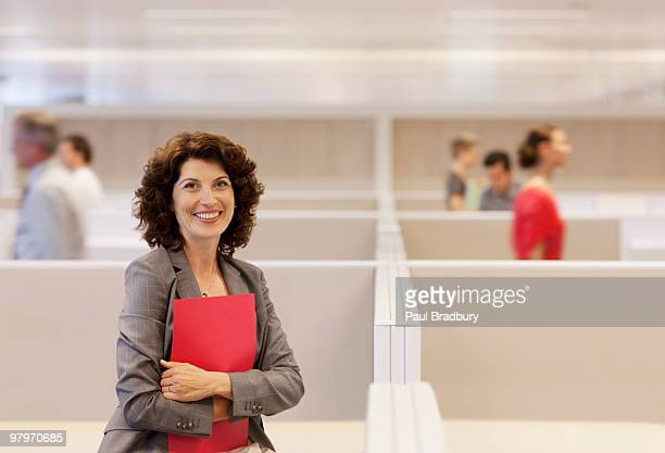 Businesswoman holding folder in office cubicle