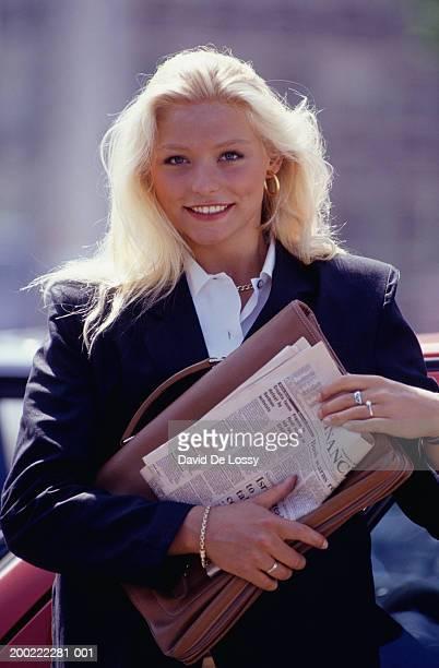 Businesswoman holding folders, portrait
