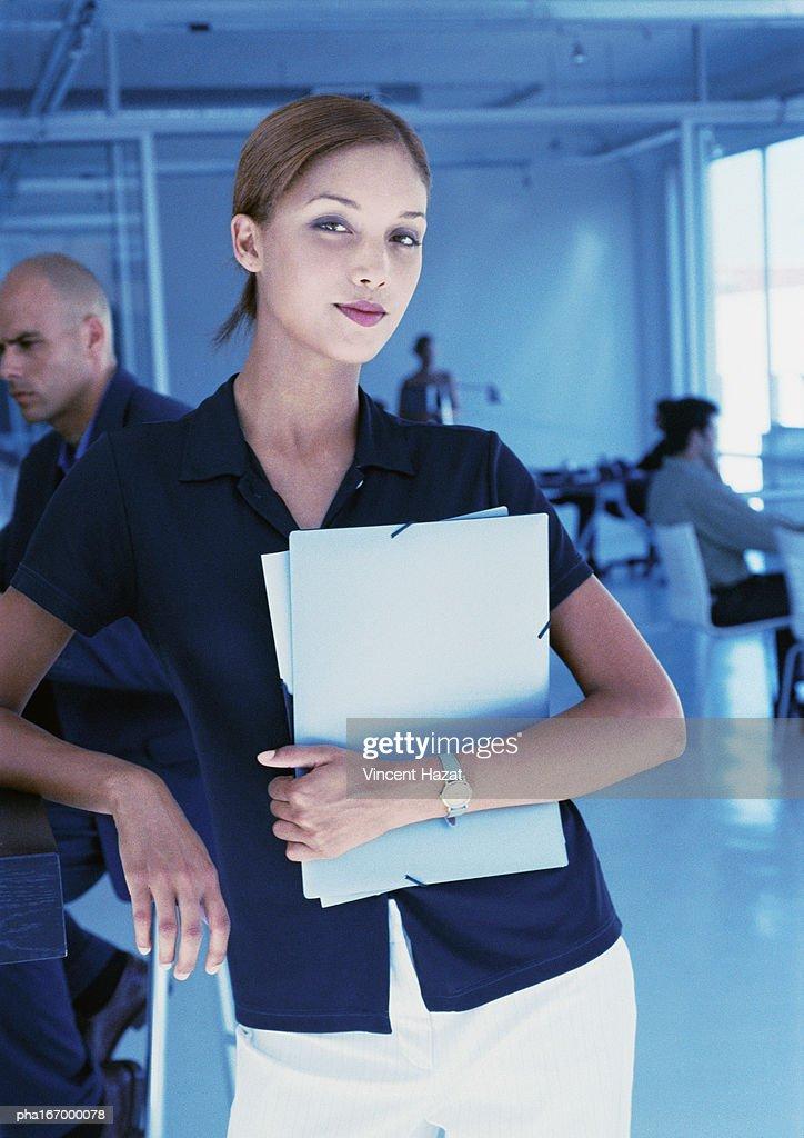Businesswoman holding folders, portrait : Stockfoto