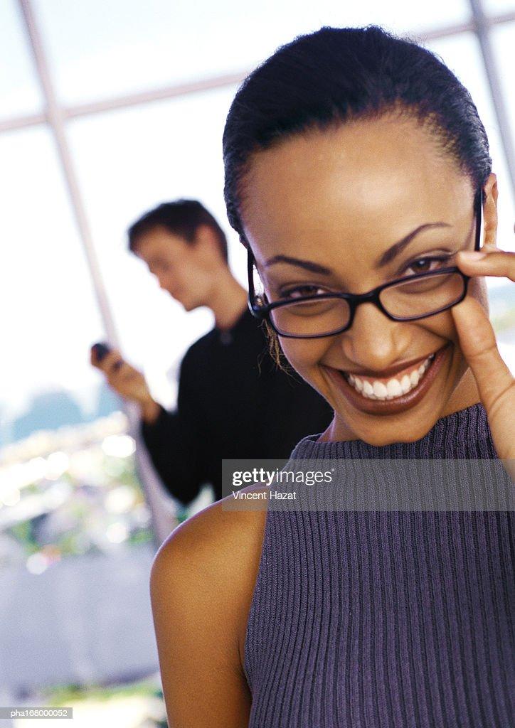 Businesswoman holding glasses, smiling, portrait : Stockfoto