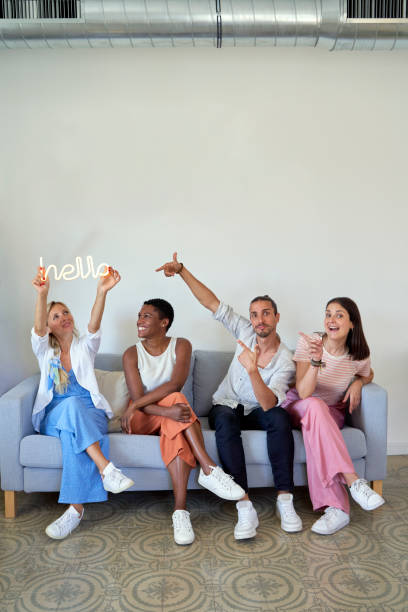Businesswoman holding Hello word sign while sitting with coworkers on sofa
