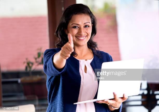 femme d'affaires retenant l'ordinateur portatif et donnant des pouces vers le haut - satisfaction photos et images de collection