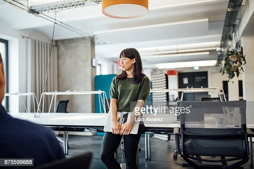 Businesswoman holding laptop in meeting
