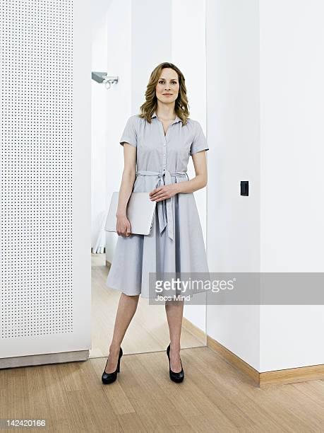 businesswoman holding laptop, smiling