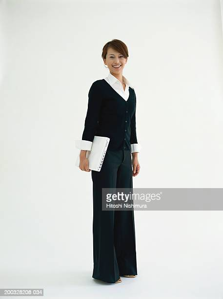 Businesswoman holding laptop, smiling