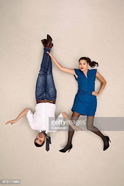 Businesswoman holding male colleague upside down