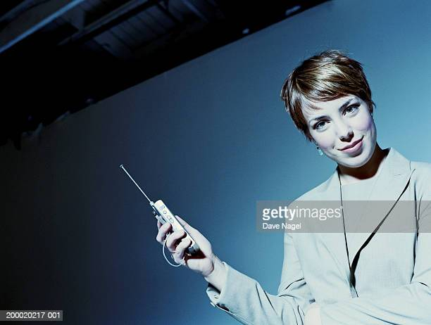 businesswoman holding mobile phone, portrait - gel effect lighting stock photos and pictures