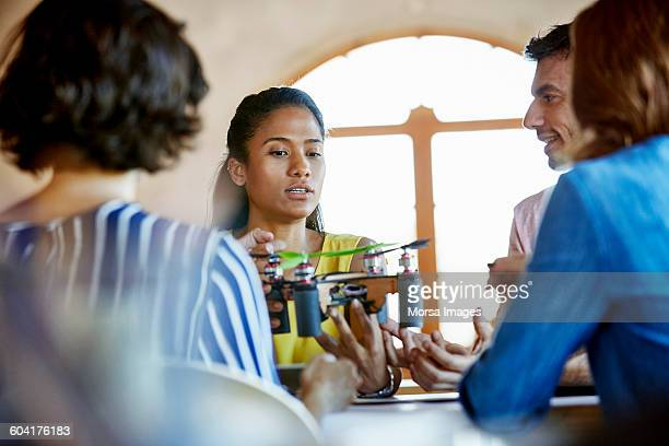 businesswoman holding octocopter during meeting - vanguardians stock pictures, royalty-free photos & images