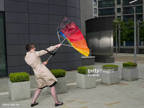 Businesswoman holding onto umbrella turned inside out in wind