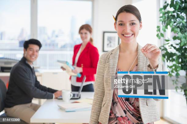 Businesswoman holding Open sign in office