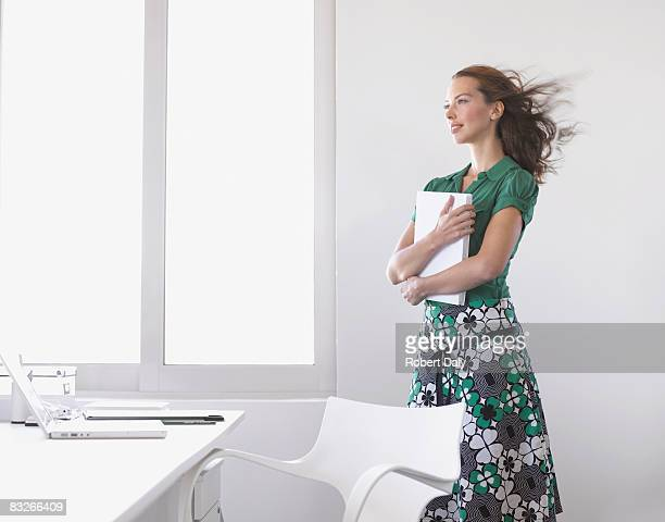 Businesswoman holding paperwork with wind blowing