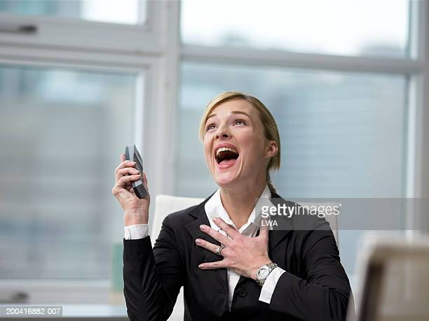 Businesswoman holding phone, screaming, hand on heart