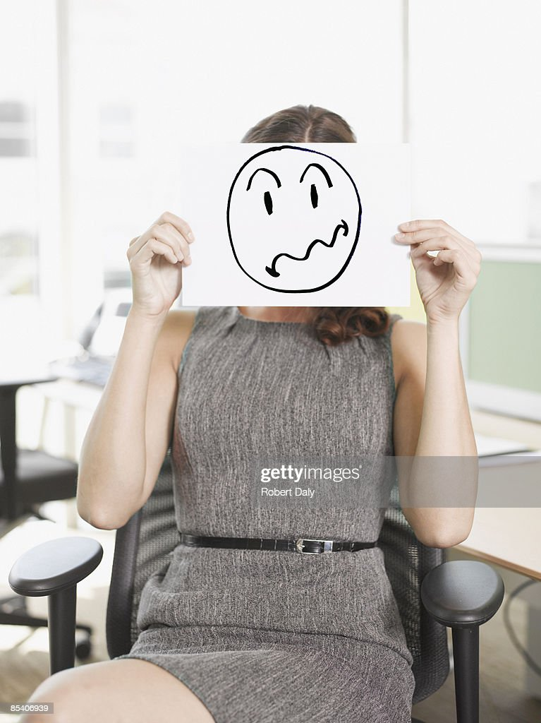 Businesswoman holding picture of frustrated face : Stock Photo