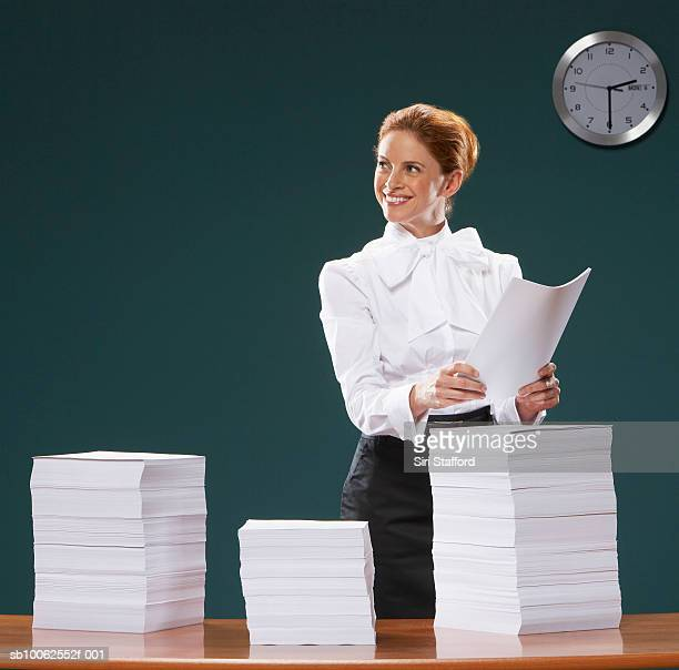 Businesswoman holding sheets of paper, looking away, smiling