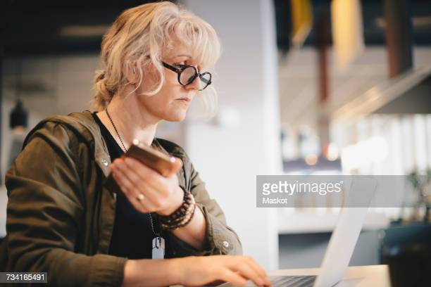 Businesswoman holding smart phone while using laptop at desk in office