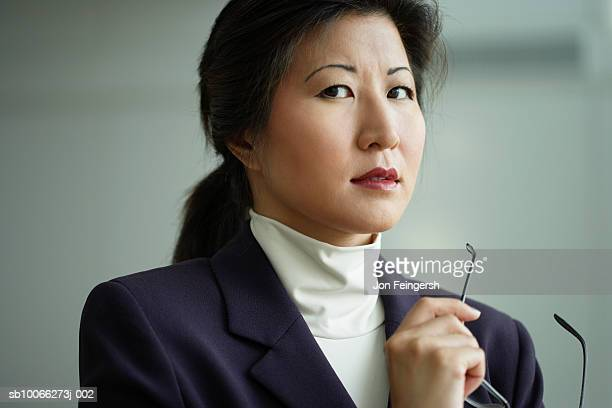 Businesswoman holding spectacles, portrait, close-up
