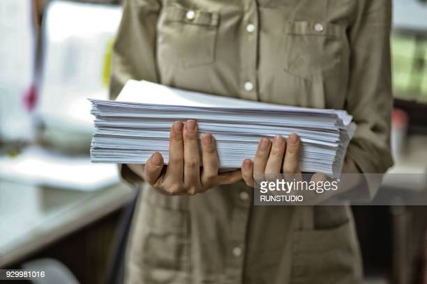 Businesswoman holding stack of documents in office