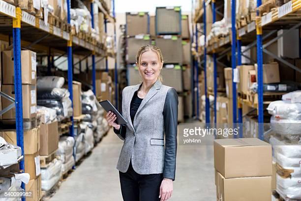 Mulher de Negócios exploração tablet e sorridente no armazém
