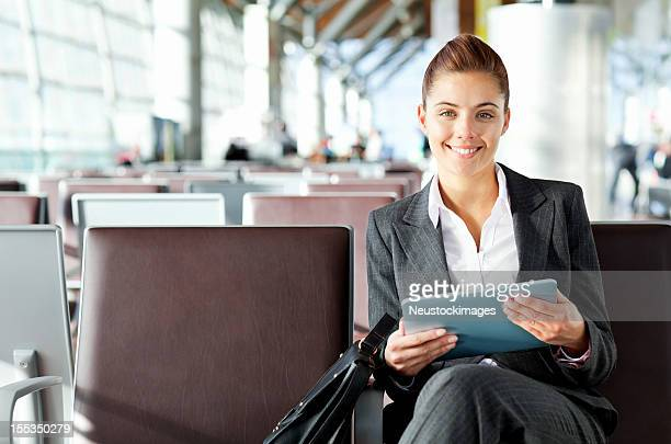 Businesswoman Holding Tablet Computer In Departure Lounge