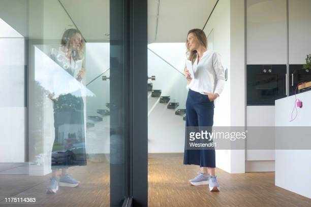 businesswoman holding tablet in modern home looking out of window - bluse stock-fotos und bilder