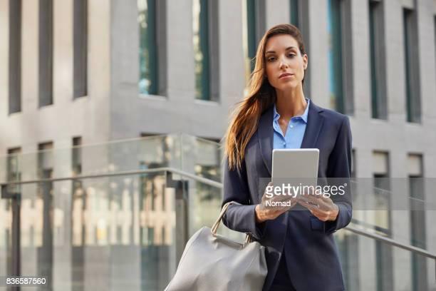 Businesswoman holding tablet PC against building