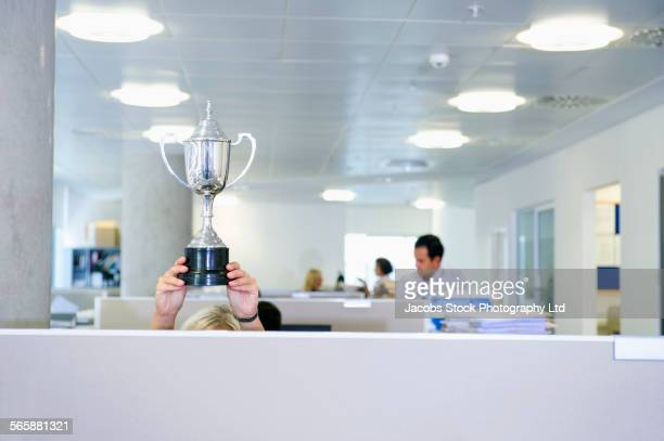 businesswoman holding trophy over office cubicle - award stockfoto's en -beelden