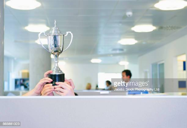 businesswoman holding trophy over office cubicle - award stock pictures, royalty-free photos & images