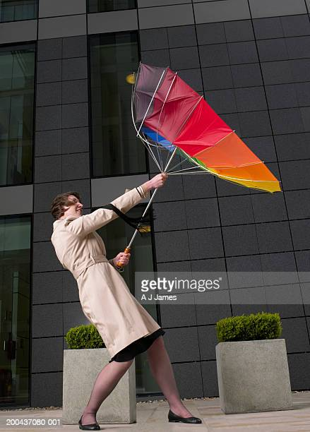 Businesswoman holding umbrella turned inside out in windy weather