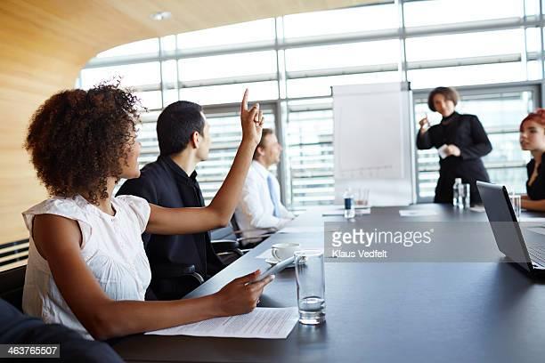 businesswoman holding up hand at meeting - roupa formal - fotografias e filmes do acervo