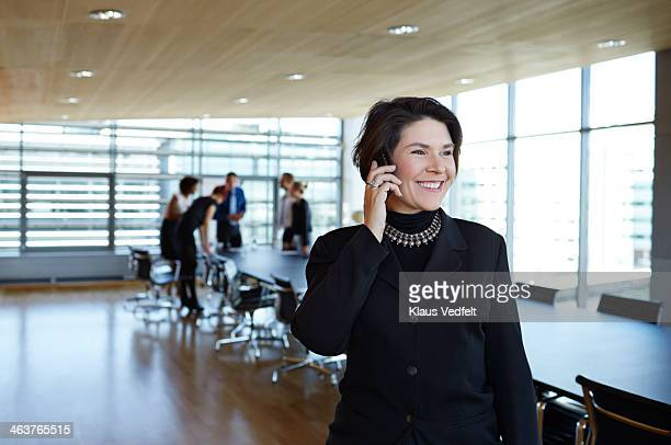 Businesswoman holding up phone, coworkers in back