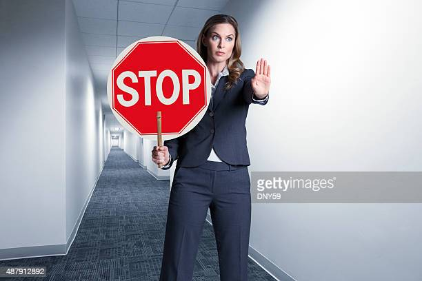Businesswoman Holding Up Stop Sign In Office Hallway