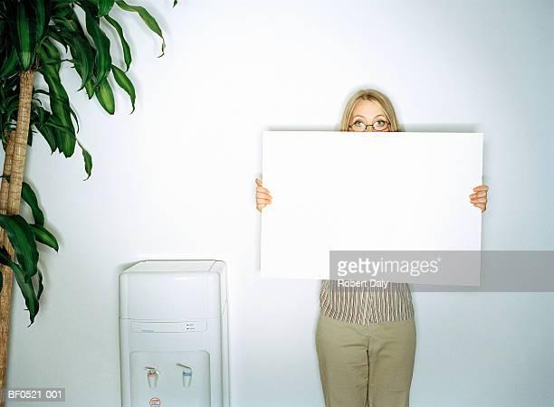 Businesswoman holding up whiteboard, portrait