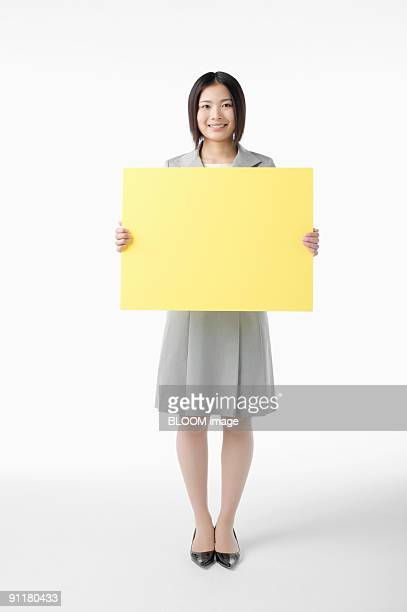 Businesswoman holding yellow board, studio shot