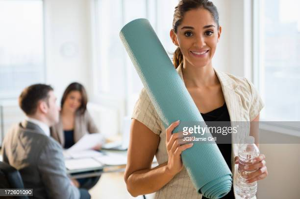 Businesswoman holding yoga mat in office