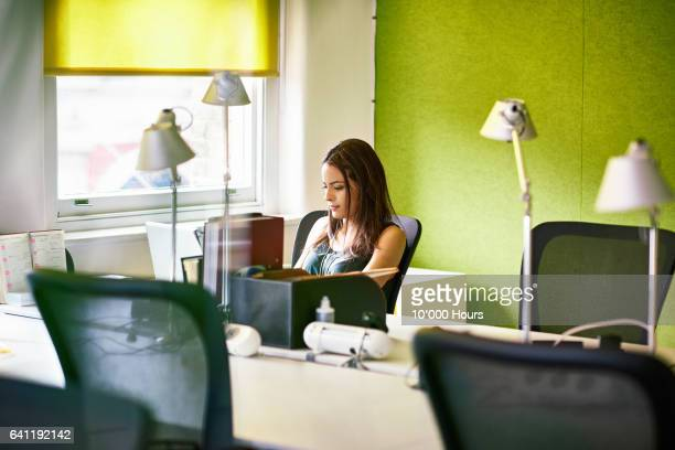 Businesswoman hot desking in a business start-up office