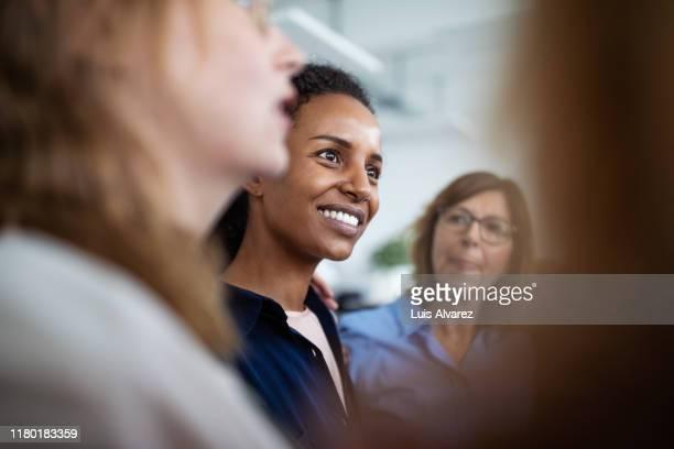 businesswoman huddling with colleagues in office - femmes d'âge moyen photos et images de collection