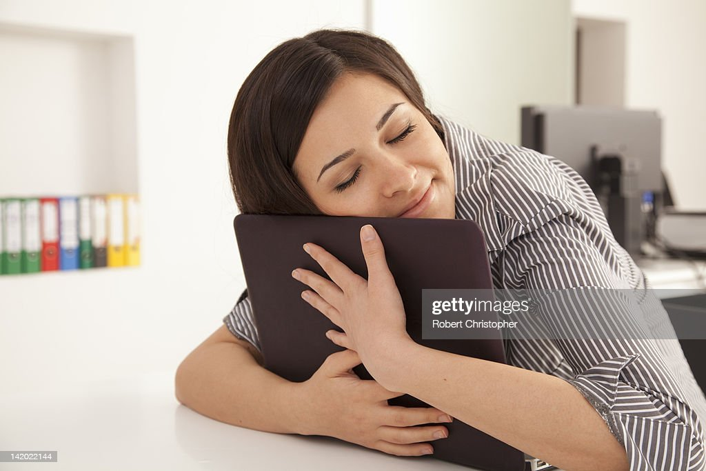Businesswoman hugging computer in office : Stock Photo