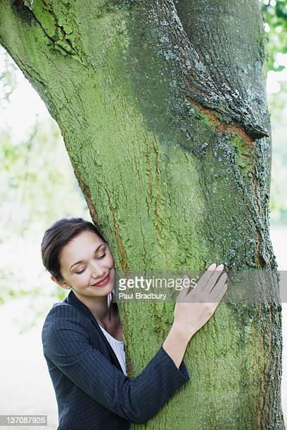 businesswoman hugging tree - tree hugging stock pictures, royalty-free photos & images