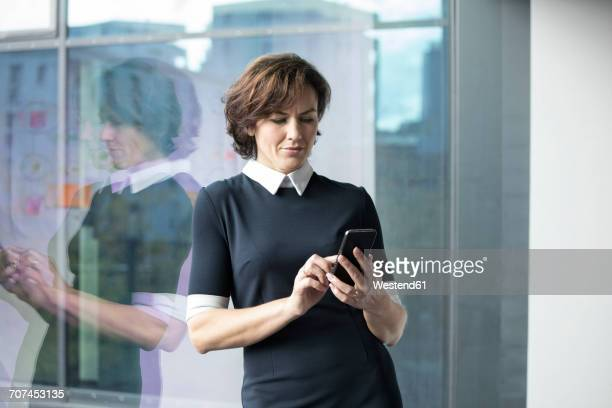 Businesswoman husing cell phone at the window