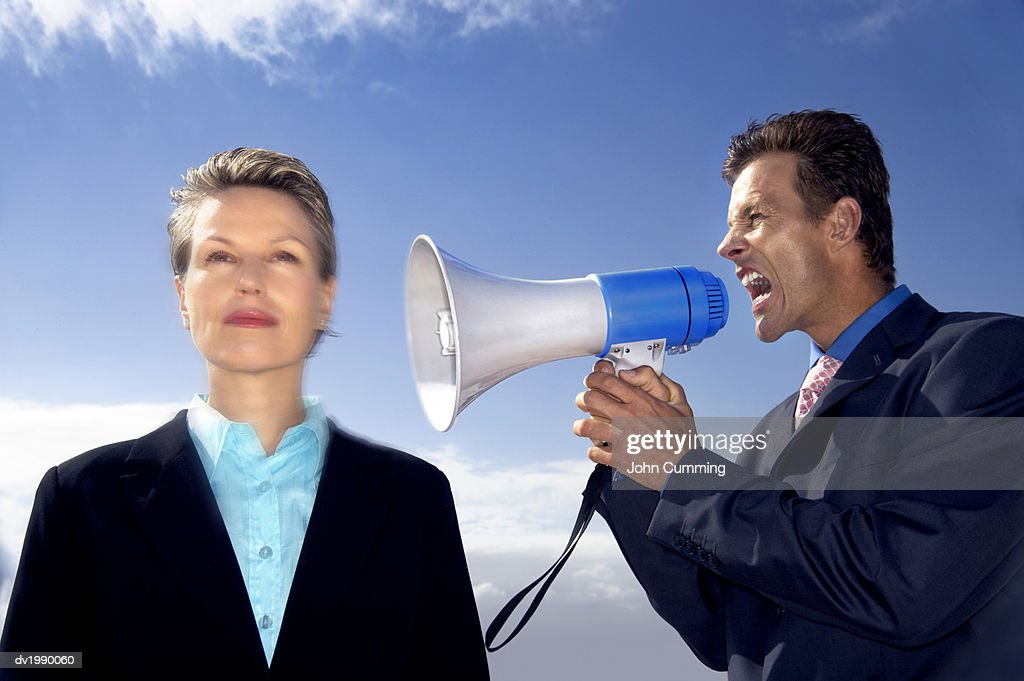 Businesswoman Ignoring a Businessman Shouting at Her Through a Megaphone : Stock Photo