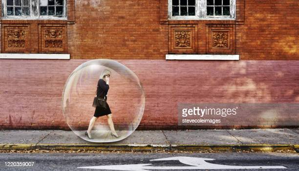 businesswoman in a bubble walking on sidewalk. - protection stock pictures, royalty-free photos & images