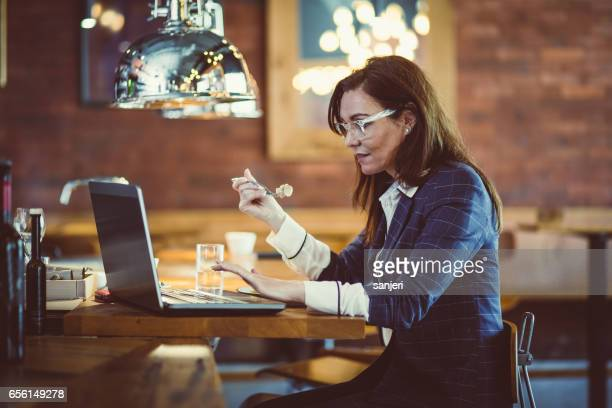 Businesswoman in a Cafe Restaurant Working on Laptop During Lunch