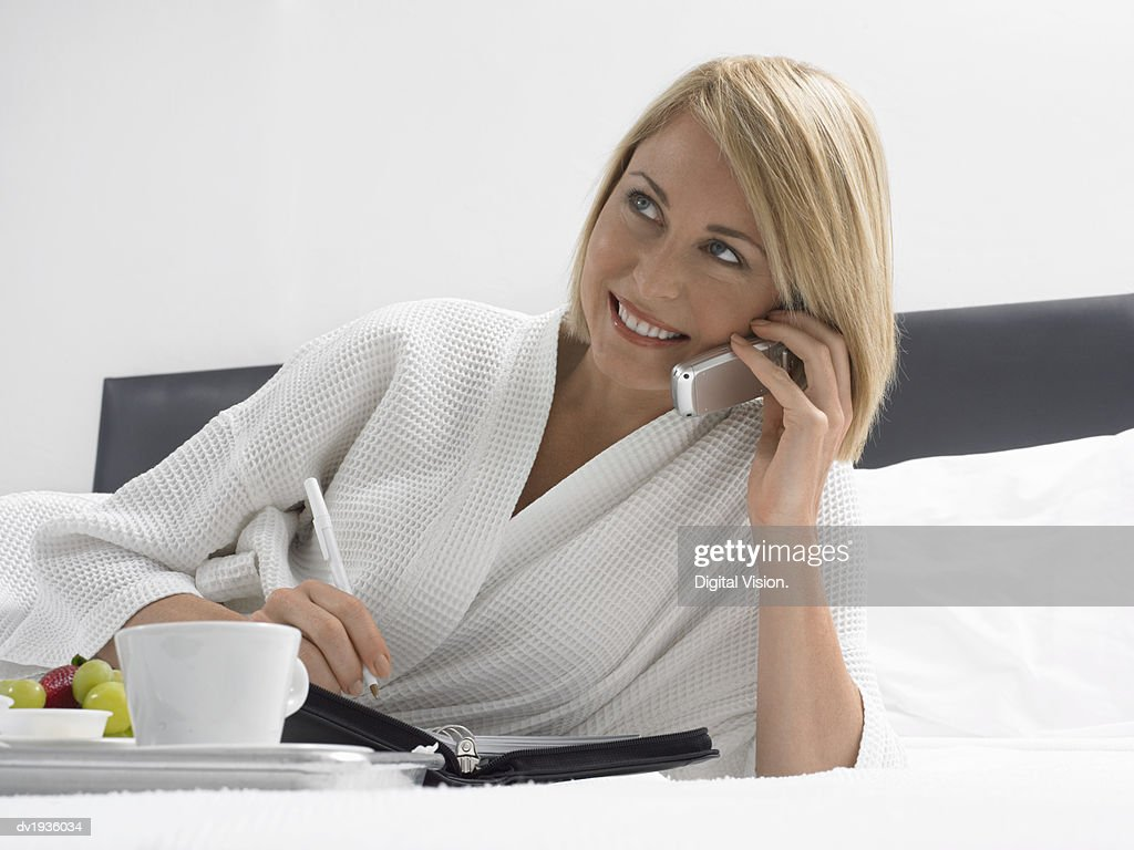 Businesswoman in a Dressing Gown Lying on a Bed and Using a Mobile Phone : Stock Photo