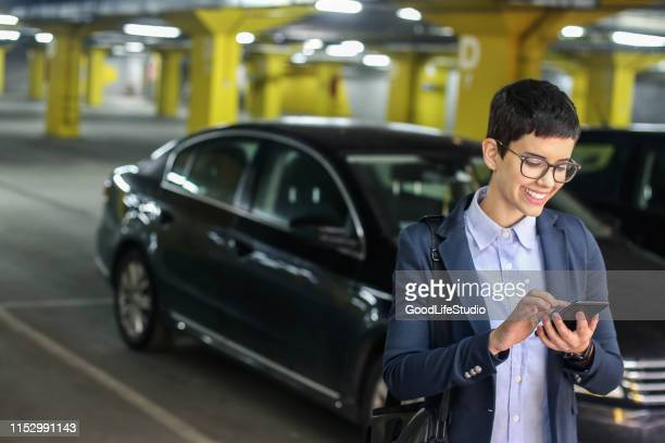 businesswoman in a parking garage - parking garage stock pictures, royalty-free photos & images