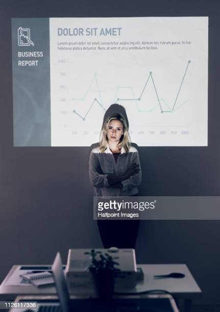 a businesswoman in an office, standing against a wall and a projection screen. - プロジェクター ストックフォトと画像